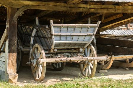 old wood farm wagon: Old Romanian Wagon (Caruta) In Traditional Farm Barn