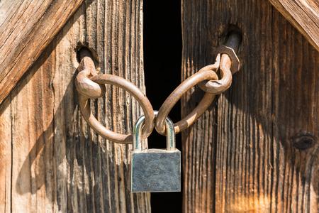 Wood Door Locked With Metal Padlock photo