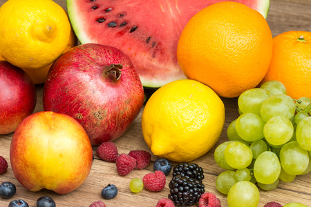 Watermelon, Pomegranate, Oranges, Lemons, Peaches, Grapes And Berries Summer Fruits On Wood Table