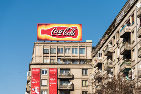 coke bottle: BUCHAREST, ROMANIA - DECEMBER 12, 2014: Coca-Cola Advertising on Apartment Buildings Downtown. Is a carbonated soft drink sold in stores and restaurants in every country except Cuba and North Korea.