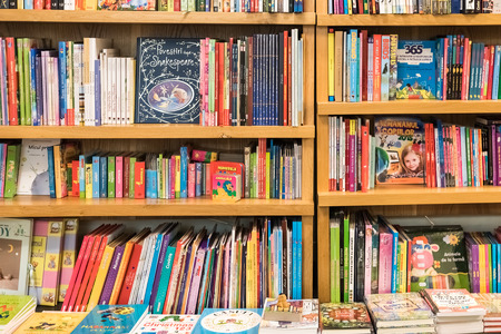 library background: BRASOV, ROMANIA - DECEMBER 22, 2014: Bookshelf In Library With Many International Books For Sale.