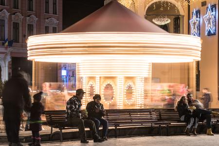 BRASOV, ROMANIA - DECEMBER 22, 2014:  People Having Fun On Christmas Fairground Carousel Downtown Brasov City At Night.