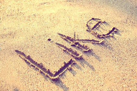 symbol tourism: Retro Photo Of The Word Like Written On Sand