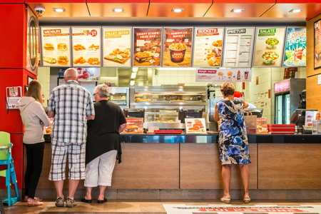 food products: TIMISOARA, ROMANIA - AUGUST 25, 2014: People Order Kentucky Fried Chicken In Fast-Food Restaurant. It is a fast food restaurant chain headquartered in United States specialized in chicken products. Editorial