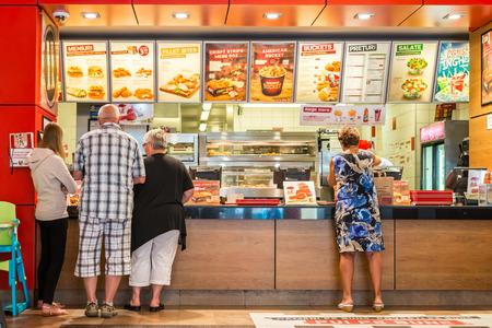 logo de comida: TIMISOARA, Rumania - 25 de agosto 2014: La gente Orden Kentucky Fried Chicken En Fast-Food Restaurant. Es una cadena de restaurantes de comida r�pida con sede en Estados Unidos especializada en productos de pollo.