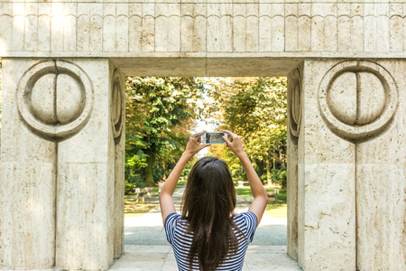 constantin: Young Girl Taking Photography Of The Gate of the Kiss Stone Sculpture Made By Constantin Brancusi in 1938 In Targu Jiu, Romania. Stock Photo