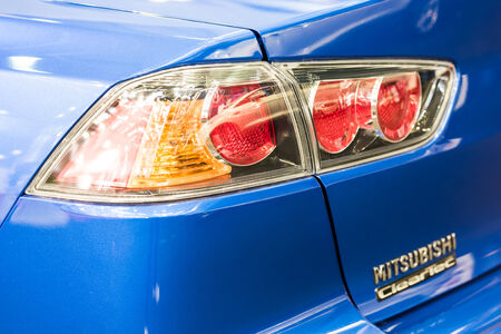 headquartered: BUCHAREST, ROMANIA - OCTOBER 31, 2014: Mitsubishi Tail Light Close Up. Founded in 1970 Mitsubishi Motors Corporation is a multinational automotive manufacturer headquartered in Tokyo, Japan.