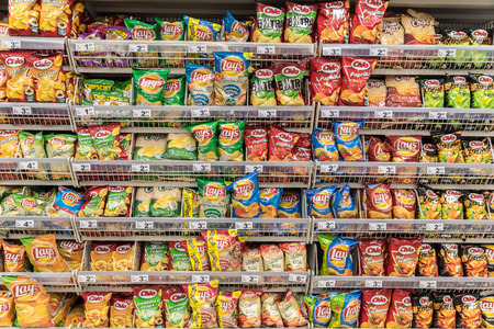 shopping binge: BUCHAREST, ROMANIA - JANUARY 20, 2015: Unhealthy Fast Food Snacks For Sale On Supermarket Shelf. Editorial