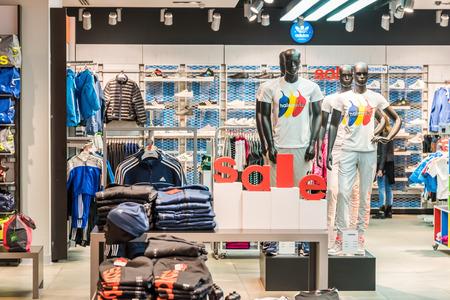 adentro y afuera: BUCAREST, RUMANIA - 28 de enero de 2015: Ventas de descuento en la tienda Adidas. Adidas es una multinacional alemana que diseña y fabrica ropa deportiva y accesorios con sede en Alemania. Editorial