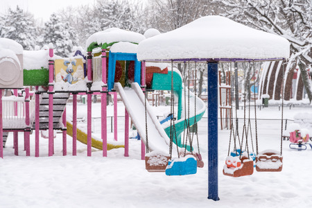 Children Playground In Public Park Covered With Winter Snow photo