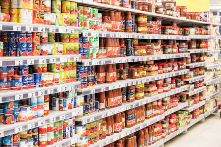 canned goods: BUCHAREST, ROMANIA - MARCH 01, 2015: Canned Food And Special Sauces For Sale On Supermarket Stand.