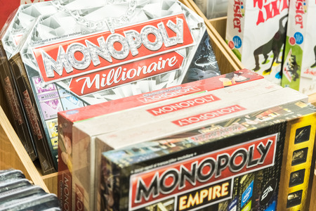 monopoly money: BUCHAREST, ROMANIA - MARCH 22, 2015: Monopoly Game For Sale On Library Shelf. Monopoly is a board game that originated in the United States in 1903 as a way to demonstrate the evils of land ownership