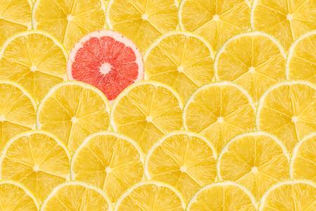 Egy Pink Grapefruit szelet kiemelkedik Sárga citrom szeletek Stock fotó