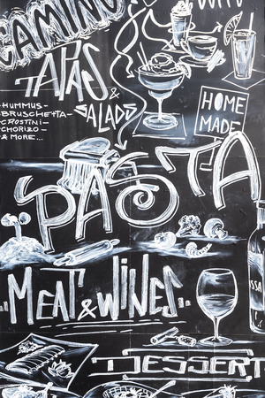 CLUJ NAPOCA, ROMANIA - APRIL 13, 2015: Restaurant Food Menu Design On Black Chalkboard At Local Restaurant In The Museum Square Of Cluj Napoca.