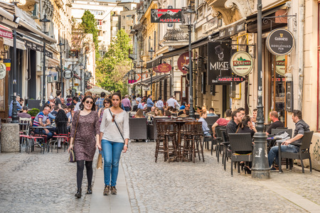 outdoor restaurant: BUCHAREST ROMANIA  MAY 18 2015: Tourists Visiting And Having Lunch At Outdoor Restaurant Cafe Downtown Lipscani Street one of the most busiest streets of central Bucharest. Editorial