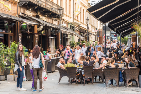 BUCHAREST ROMANIA  MAY 18 2015: Tourists Visiting And Having Lunch At Outdoor Restaurant Cafe Downtown Lipscani Street one of the most busiest streets of central Bucharest. Éditoriale