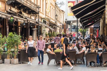 BUCHAREST ROMANIA  MAY 18 2015: Tourists Visiting And Having Lunch At Outdoor Restaurant Cafe Downtown Lipscani Street one of the most busiest streets of central Bucharest. Redactioneel
