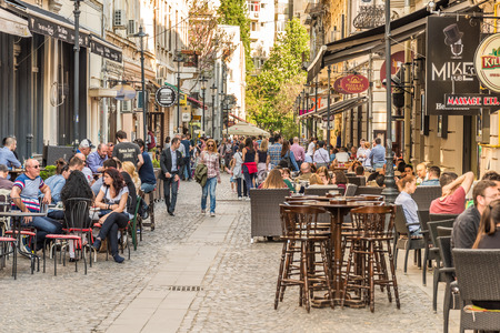 BUCHAREST ROMANIA  MAY 18 2015: Tourists Visiting And Having Lunch At Outdoor Restaurant Cafe Downtown Lipscani Street one of the most busiest streets of central Bucharest. 報道画像