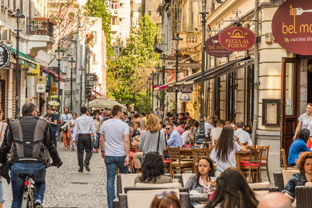BUCHAREST ROMANIA  MAY 18 2015: Tourists Visiting And Having Lunch At Outdoor Restaurant Cafe Downtown Lipscani Street one of the most busiest streets of central Bucharest. 新闻类图片