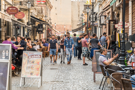 having lunch: BUCHAREST ROMANIA  MAY 18 2015: Tourists Visiting And Having Lunch At Outdoor Restaurant Cafe Downtown Lipscani Street one of the most busiest streets of central Bucharest. Editorial