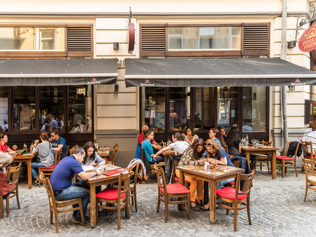 outdoor restaurant: BUCHAREST ROMANIA  MAY 18 2015: Tourists Having Lunch At Outdoor Restaurant Downtown Lipscani Street one of the most busiest streets of central Bucharest. Editorial