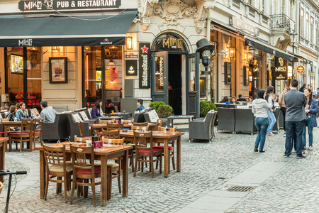 BUCHAREST ROMANIA  MAY 31 2015: Tourists Visiting And Having Lunch At Outdoor Restaurant Cafe Downtown Lipscani Street one of the most busiest streets of central Bucharest. Redactioneel
