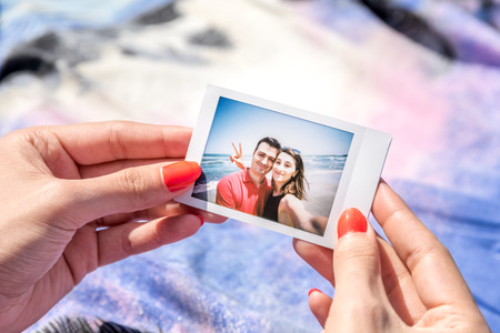 Girl Holding Instant Photo Of Young Happy Couple Stockfoto