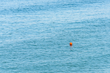 flotation: Orange Life Buoy Floating In The Middle Of The Ocean