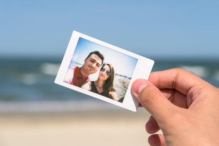 young happy couple: Man Holding Instant Photo Of Young Happy Couple