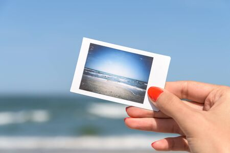 beach landscape: Girl Holding Instant Photo Of Sea Beach Landscape
