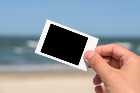 hand holding paper: Man Hand Holding Blank Instant Photo Card On Beach In Summer Stock Photo