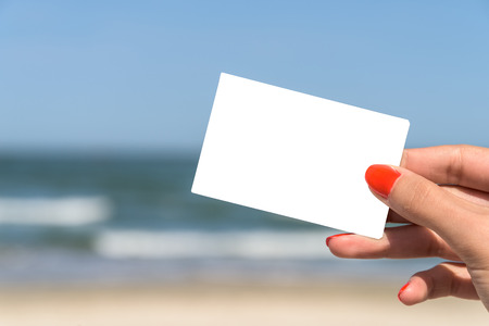 white card: Girl Hand Holding Blank White Card On Beach In Summer Stock Photo