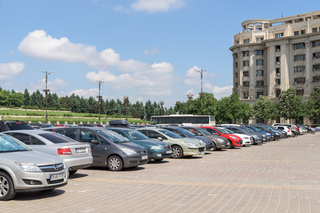 a lot: BUCHAREST, ROMANIA - JULY 26, 2015: Cars In Car Parking Lot In Front Of Parliament Palace Casa Poporului Or House Of The People In Bucharest.