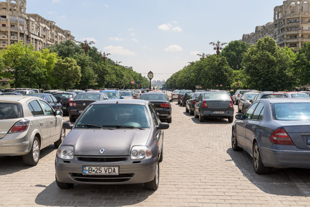 a lot  of: BUCHAREST, ROMANIA - JULY 26, 2015: Cars In Car Parking Lot In Front Of Parliament Palace Casa Poporului Or House Of The People In Bucharest.