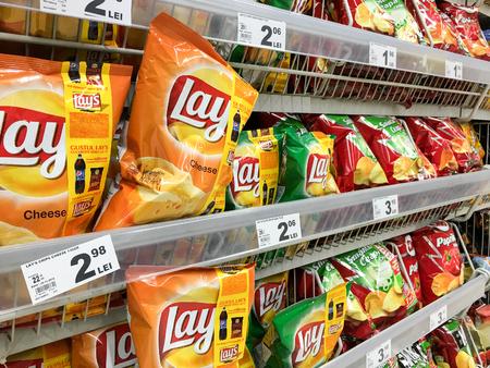 shopping binge: BUCHAREST, ROMANIA - DECEMBER 21, 2015: Fast Food Snacks For Sale On Supermarket Shelf.