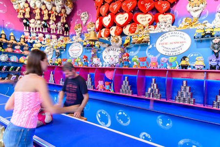 knockdown: VIENNA, AUSTRIA - AUGUST 09, 2015: People Having Fun On Can Knockdown Game In Wurstelprater Amusement Park or Prater In Vienna.