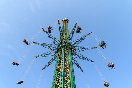 columpio: Las personas que se divierten en oscilación del carrusel Paseo Al parque de atracciones Foto de archivo