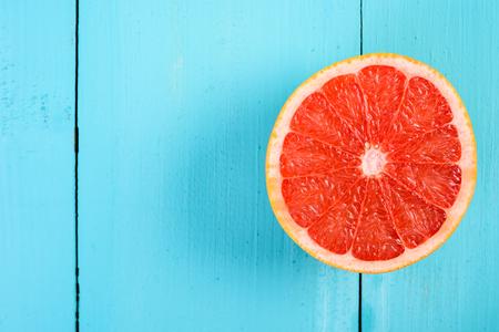 toronja: Roja fresca rodaja de pomelo en mesa de madera Foto de archivo