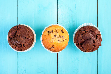 choco chips: Homemade Chocolate Chip Muffins On Blue Table Stock Photo
