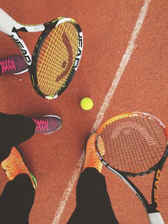 jugando tenis: Bucarest, Rumania - 15 de febrero, 2016: Los jugadores se divierte el jugar tenis en la pista. Editorial
