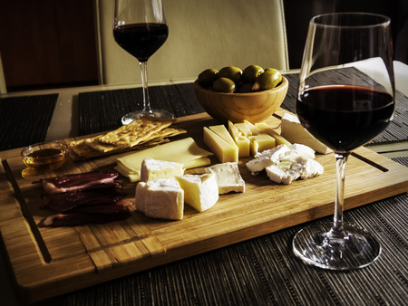 cheese platter: Camembert, Gouda And Brie Cheese Platter With Wine Glasses