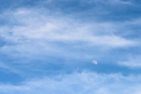 visible: Moon Visible In Daylight Blue Sky With White Soft Clouds Stock Photo