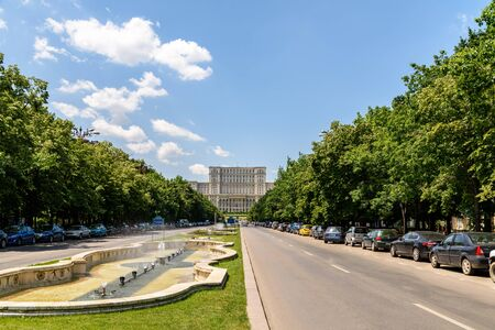 bucuresti: BUCHAREST, ROMANIA - MAY 28, 2016: Union Square Fountain And House Of The People Or Parliament Palace (Casa Poporului) View From Union Boulevard (Bulevardul Unirii) In Downtown Bucharest.
