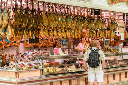 VALENCIA, SPAIN - JULY 20, 2016: Vendors Selling Ham, Bacon And Meat Products In Mercado Central (Mercat Central or Central Market), One Of The Largest Market Places In Valencia. Editorial