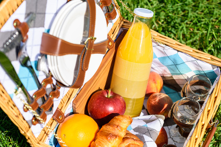 Picnic Basket With Orange Juice Bottle, Apples, Peaches, Oranges And Croissants On Green Grass In Spring Stock Photo