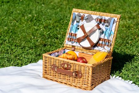 white blanket: Picnic Basket Food On White Blanket In Summer