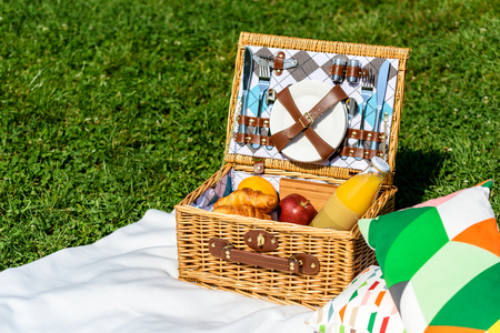 white blanket: Picnic Basket Food On White Blanket With Pillows In Summer Stock Photo