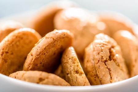 amaretto: Italian Amaretti Biscuits In White Bowl Stock Photo