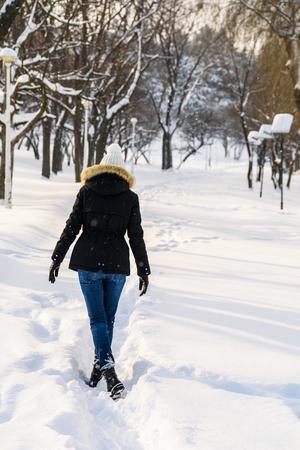 Girl Walking Through Winter Snow In Park photo