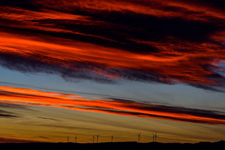 Wind Turbines Farm In The Distance On Beautiful Red, Orange And Blue Sunset Stock Photo